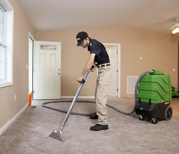 A SERVPRO employee using an extractor to pull water out of a wet carpet