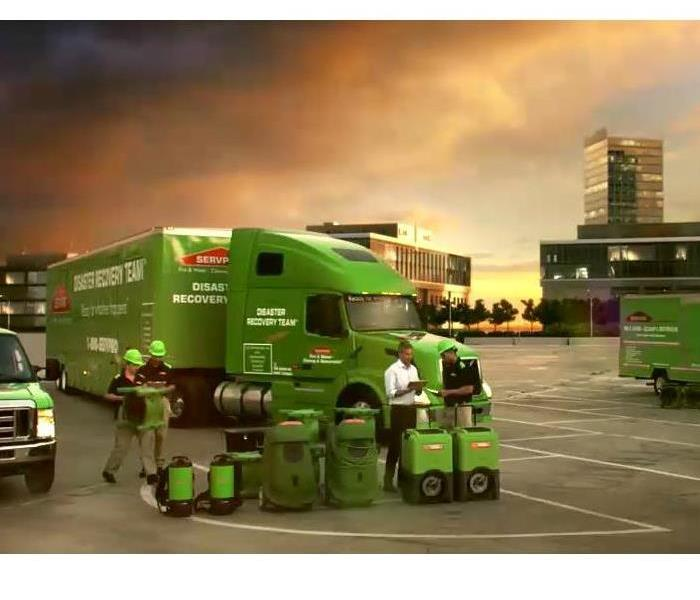 SERVPRO  employees standing near their equipment in front of a stormy sky
